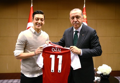 Ozil gives a signed jersey to Erdogan.
